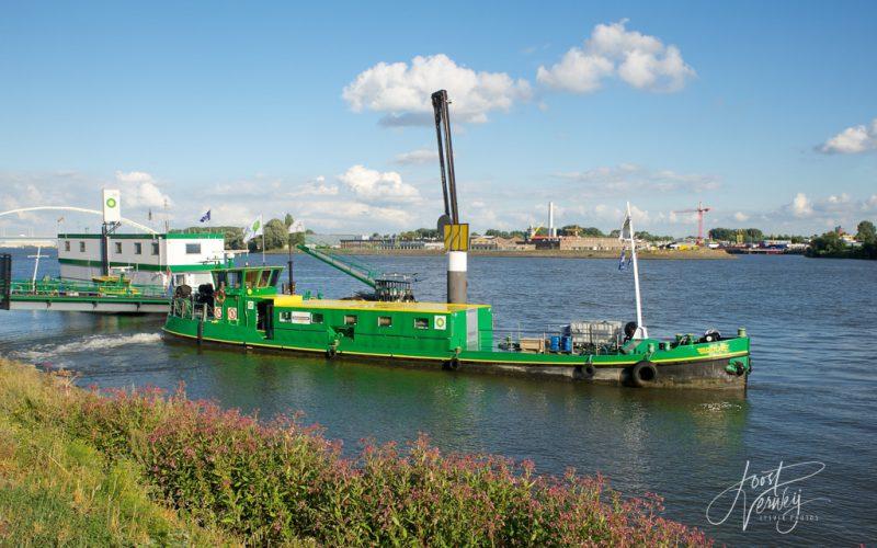 Bunkerstation op rivier de Merwede met op de achtergrond de Papendrecht brug en de N3 en een op de rivier varend binnenvaartschip.